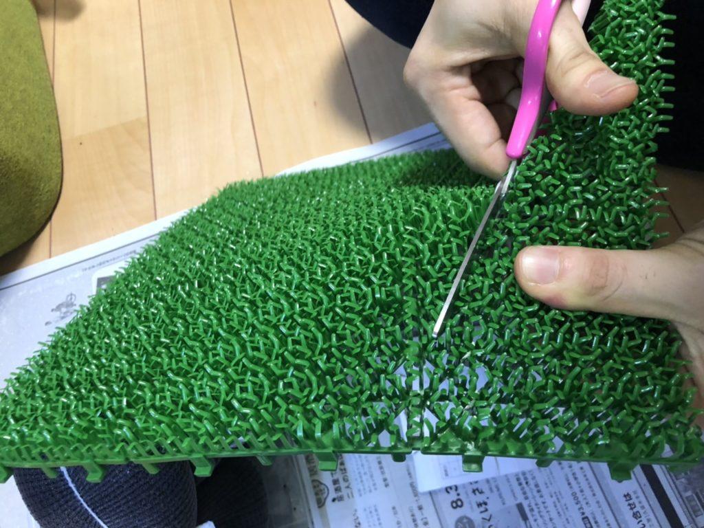 人工芝をハサミで切る